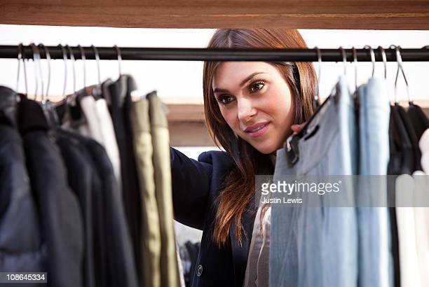 Girl sorting through a rack of male hanging clothe
