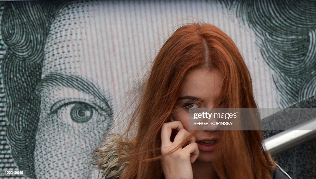 A girl speaks on a mobile phone as she stands in front of an advertising placard depicting British pounds on a warm autumn day in the Ukrainian capital of Kiev on November 12, 2012.