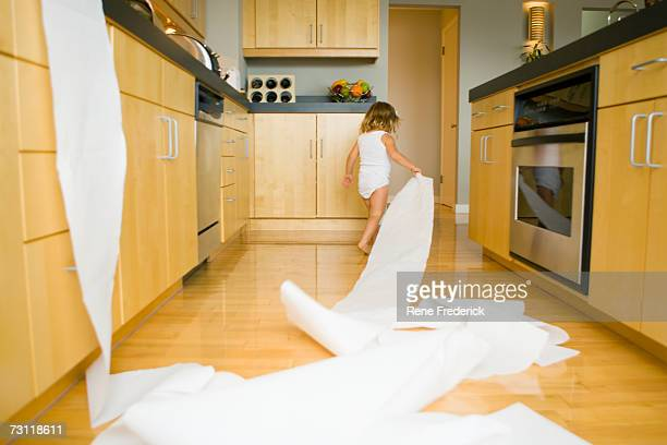 Girl (2-4) spilling roll of paper towels across kitchen floor, rear view