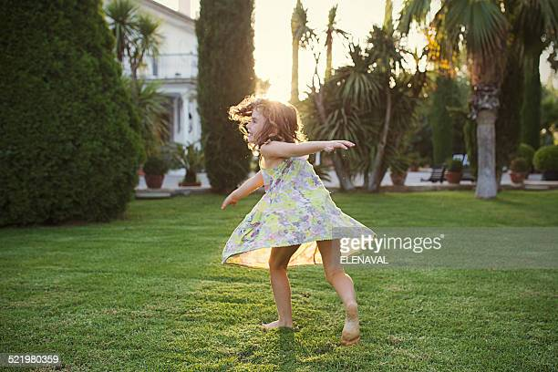 Girl (6-7) spinning around in garden