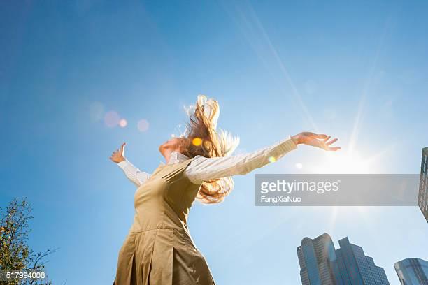 Girl spinning outside in sunshine
