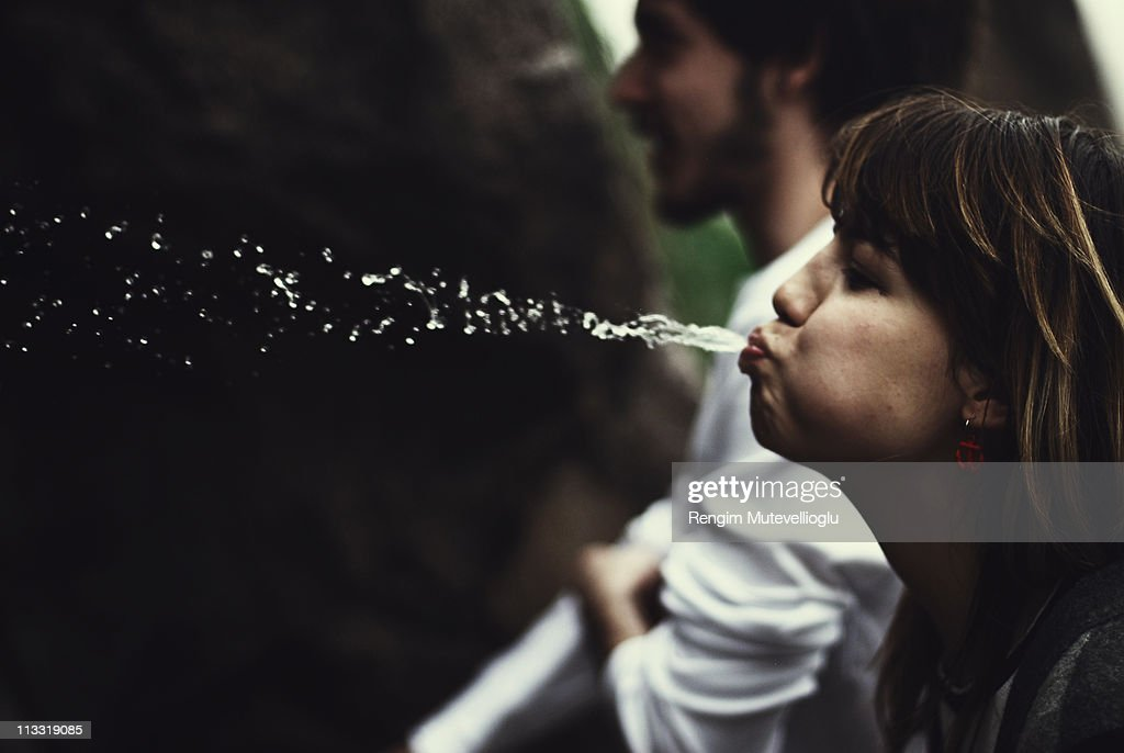 Girl spitting water : Stock Photo