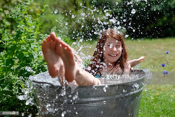 Girl splashing in a zinc tub