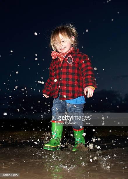 Girl splashing in puddle at night
