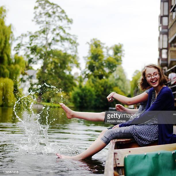 Girl splashing in river cam, on punt