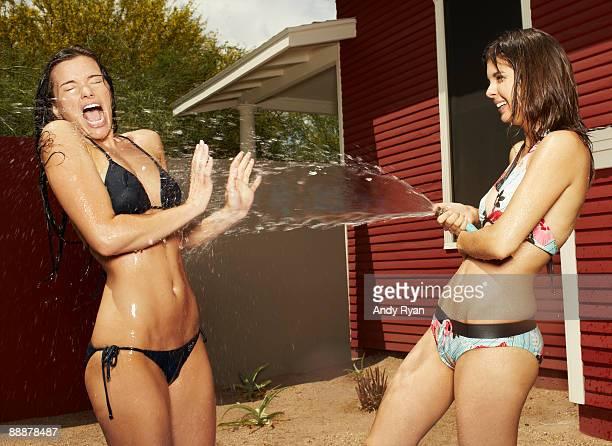 Girl Spraying Friend With Garden Hose