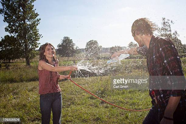 Girl sprays guy with hose in a field