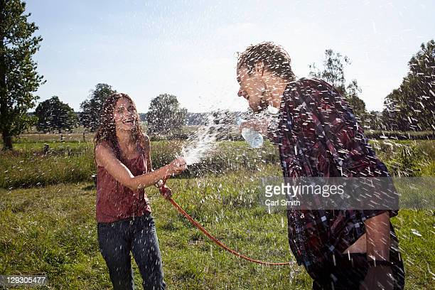 Girl sprays guy with hose on field
