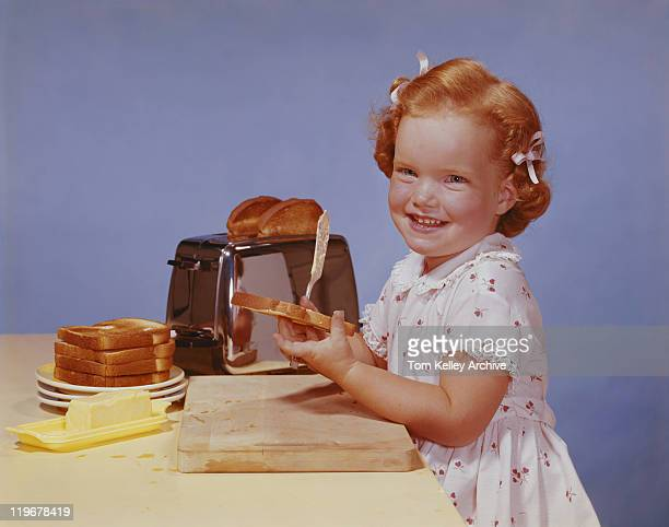 Girl spreading butter on toast, smiling, portrait