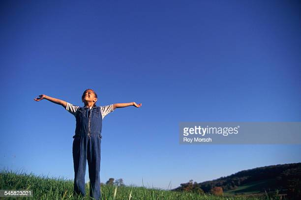 Girl Spreading out Her Arms in Meadow