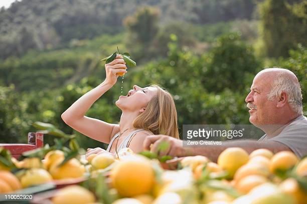 Girl squashing an orange