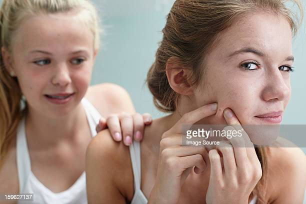 Girl squeezing a spot, friend with hand on shoulder