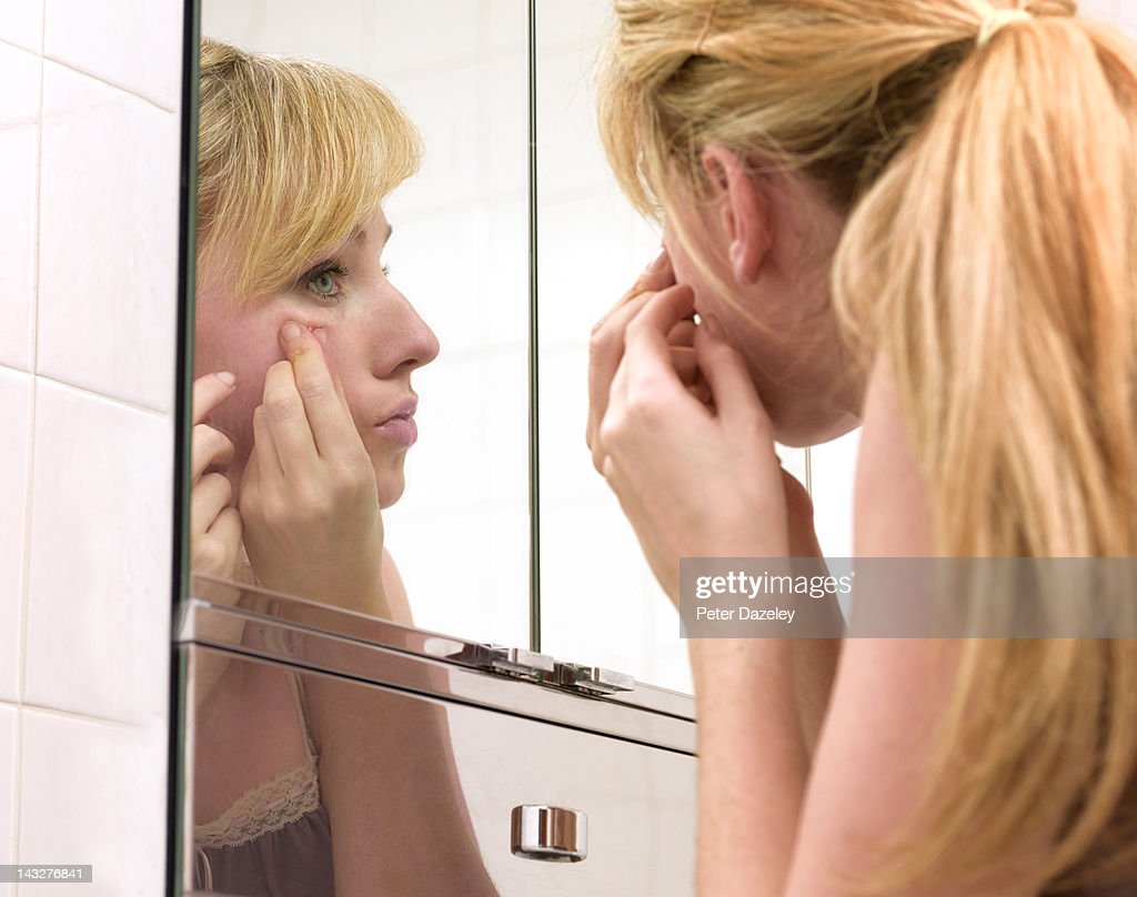 Girl squeezing a spot or pimple : Stock Photo