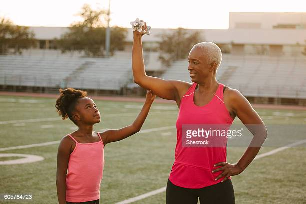Girl squeezing biceps of grandmother on football field
