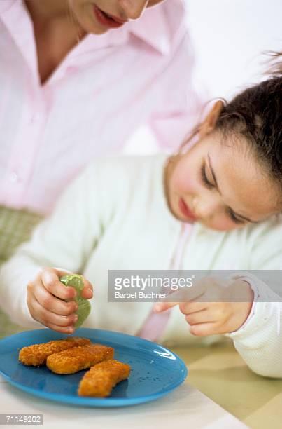 Girl (4-7) squeezing lemon over fish sticks