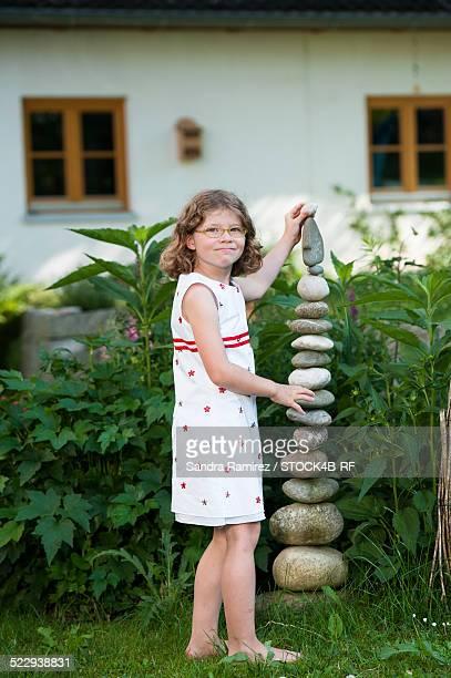 Girl stacking stones in garden