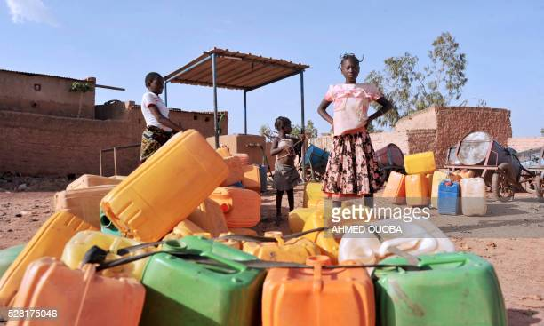 A girl stand by plastic jugs used to collect water in the poor district of Taptenga suburb of Ouagadougou on May 4 2016 Burkina Faso will impose...