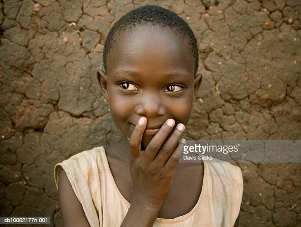 Girl (6-7) standing against mud wall, smiling, close-up