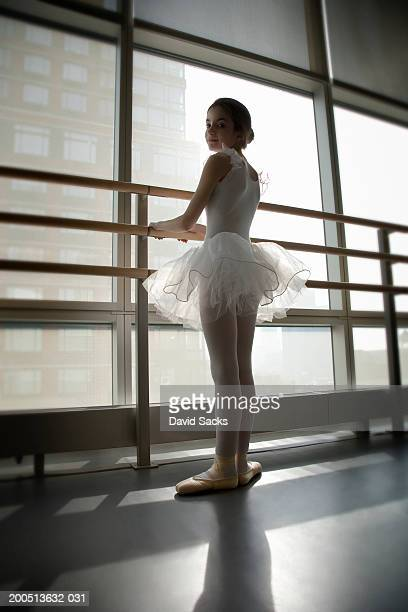 Girl (9-13) standing at bar in ballet class, portrait, rear view
