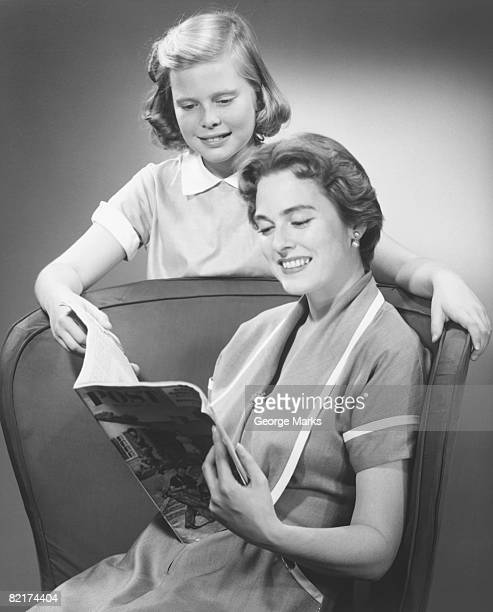 Girl (8-9) standing at mother reading magazine, (B&W)