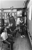 Girl standing at the blackboard while classmates and teacher look on at St Michael's School located at 82nd Street and South Shore Drive Chicago...