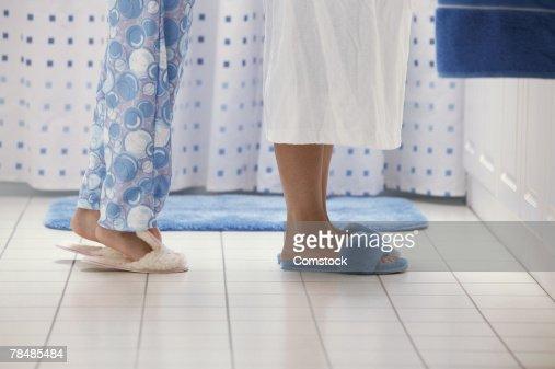 Girl standing behind mother in bathroom