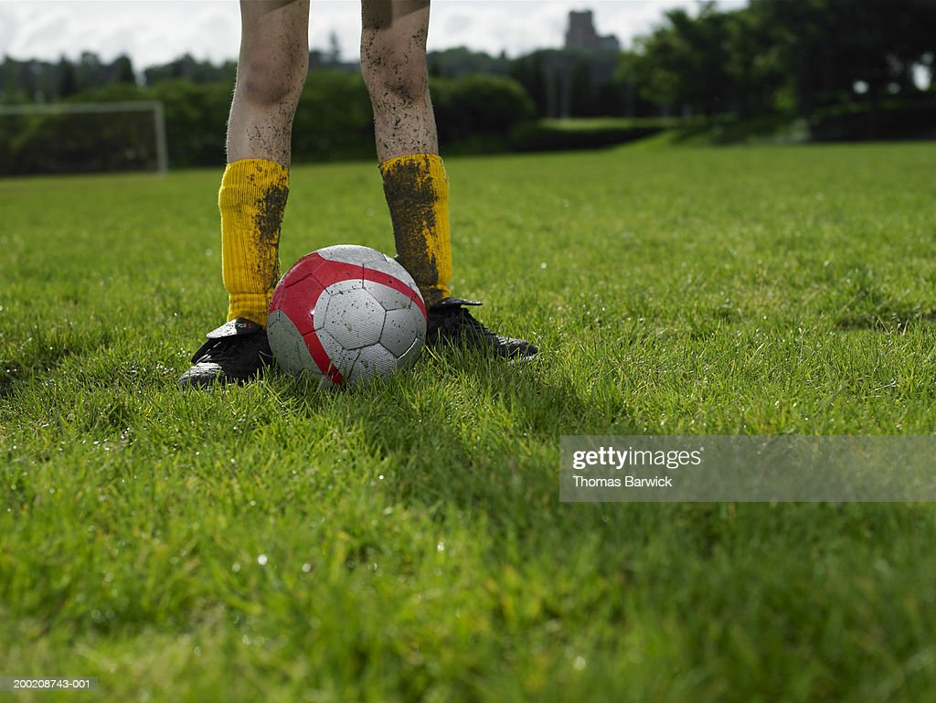Girl (10-12) standing beside soccer ball on field, low section : Stock Photo