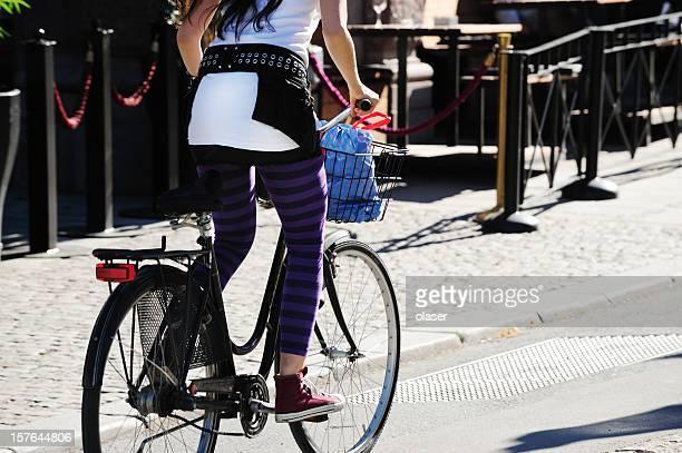 Ragazza in piedi in bicicletta in città