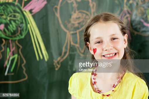 Girl standing by blackboard : Stock-Foto