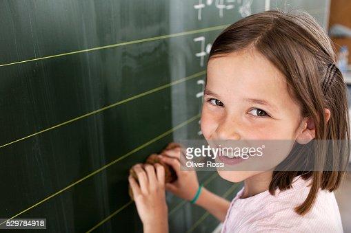 Girl standing by blackboard : Stock-Foto