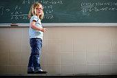 Girl Standing by Blackboard