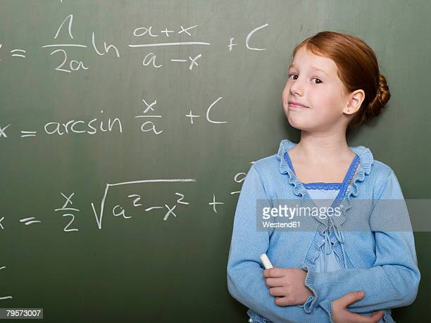 Girl (4-7) standing by blackboard, portrait, close-up