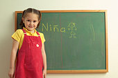 Girl standing by chalkboard with NINA on it