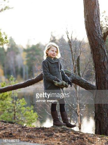 Girl standing by pine tree : Stock Photo