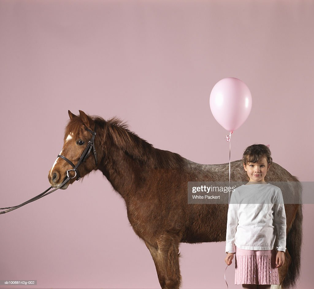 Girl (6-7) standing by pony holding balloon
