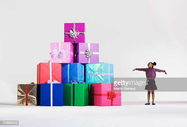 Girl (6-7) standing by stack of giant presents
