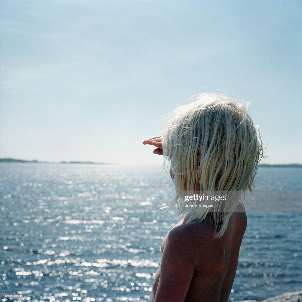 Girl standing by the ocean, Blekinge, Sweden. : Stock Photo