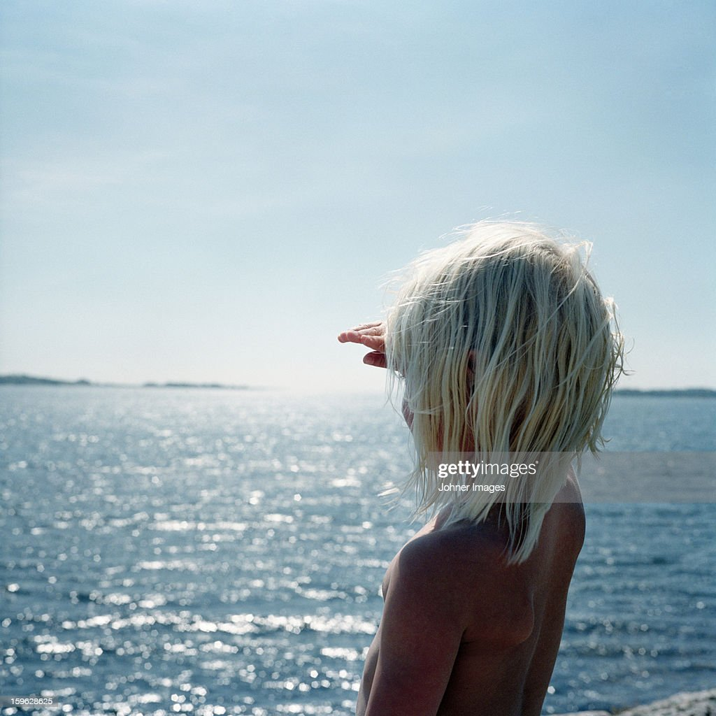 Girl standing by the ocean, Blekinge, Sweden.