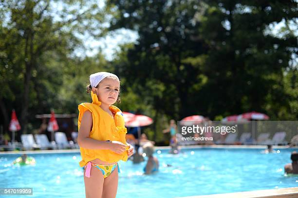 Girl standing by the pool wearing a life jacket, Thassos, Greece