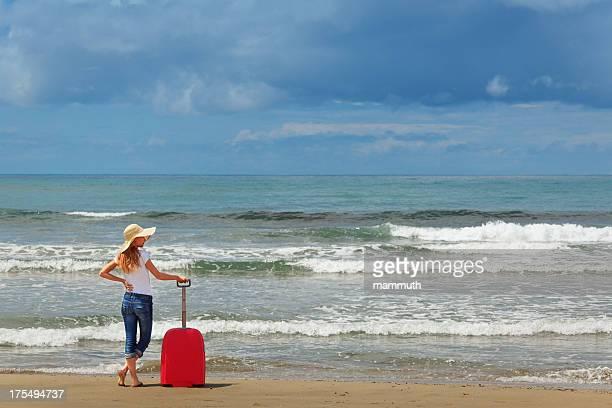 Femme debout près de la mer avec une valise
