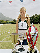 Girl (10-12) standing by trophies at school sports day, smiling