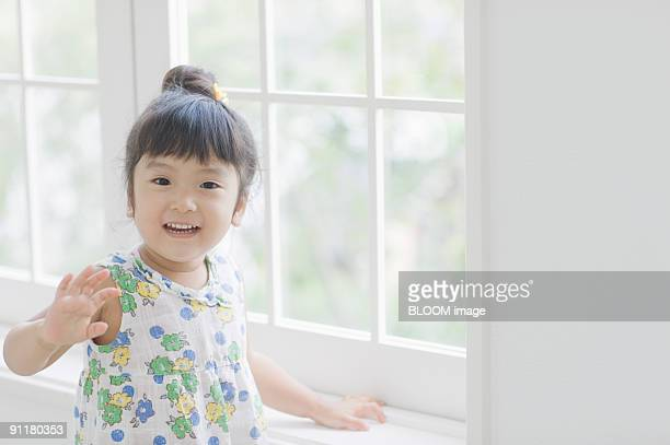 Girl standing by window, waving
