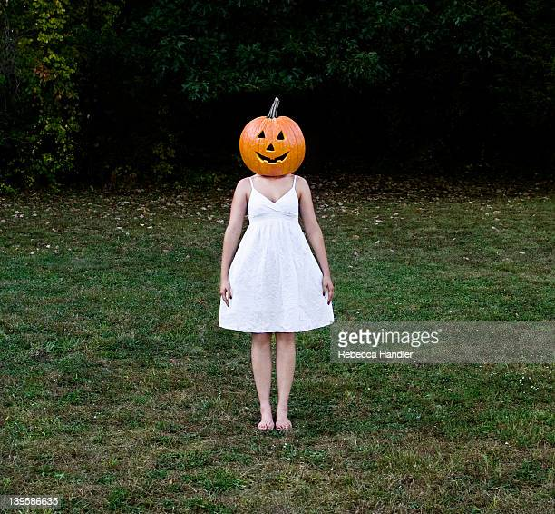 Girl standing in a field with a pumpkin head.