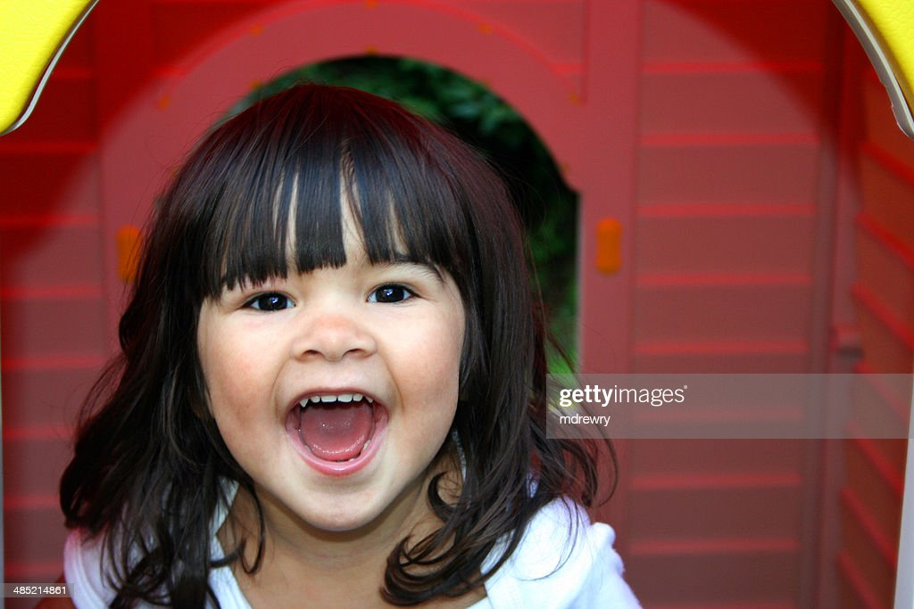 United Kingdom, England, London, Greenwich, Charlton, Portrait of laughing girl in front of wendy house : Stock Photo