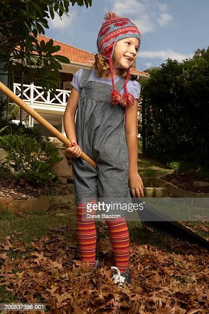 Girl (6-8)standing in autumn leaves pretending to ride rake, laughing