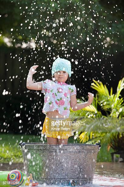 Girl standing in bubble bath in garden splashing soap bubbles