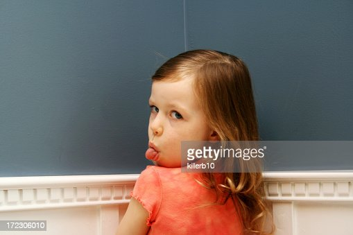 Girl standing in corner with tongue stuck out for time out