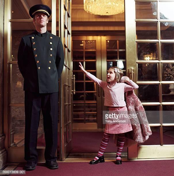 Girl (4-6) standing in doorway beside doorman
