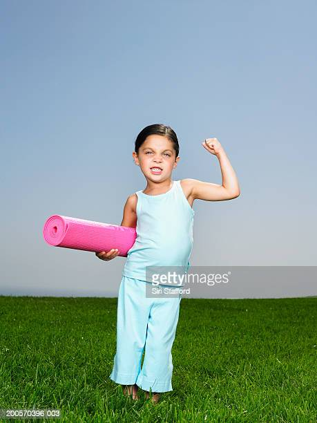 Girl (4-5) standing in field, holding exercise mat, flexing muscles