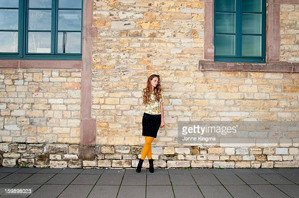 Girl standing in frond of an old building